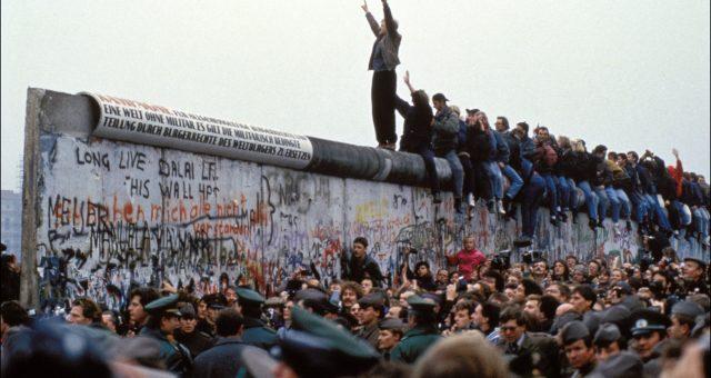 BERLIN, GERMANY - NOVEMBER 12: A man celebrates on the Berlin wall on November 12, 1989 in Berlin, Germany.(Photo by Pool CHUTE DU MUR BERLIN/Gamma-Rapho via Getty Images)